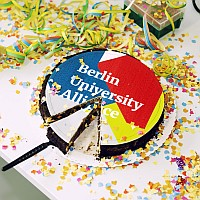 Cut cake iced with the inscription 'Berlin University Alliance' and surrounded by confetti and streamers. Photo: Matthias Heyde